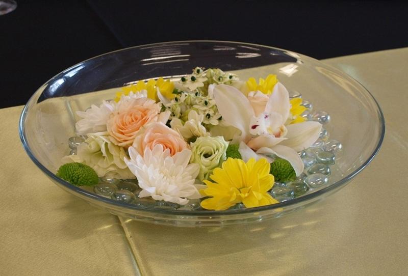 Üvegtálas asztaldísz úszó virágfejekkel